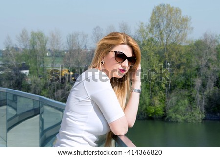 Beautiful young woman with long hair is looking at a river in the city Dusseldorf. Soft spring backlit.  - stock photo