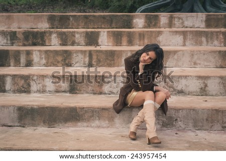 Beautiful young woman with long hair sitting on concrete steps - stock photo
