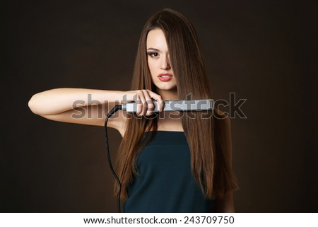 Beautiful young woman with long hair using hair straighteners on dark brown background - stock photo