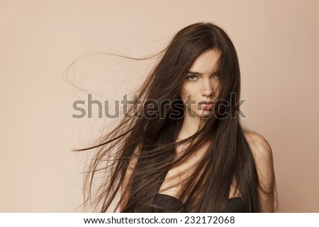 Beautiful young woman with long healthy brown hair and perfect skin - stock photo