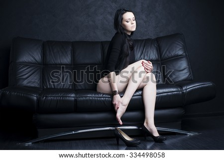 Beautiful young woman with long legs in bodysuit sitting on a black sofa. Leg pain
