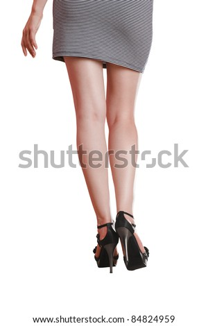 Beautiful young woman with long legs in mini dress rear view - stock photo