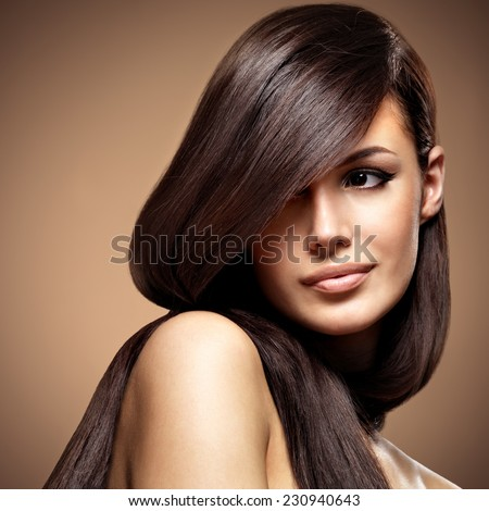 Beautiful young woman with long straight brown hair. Fashion model posing at studio over beige background