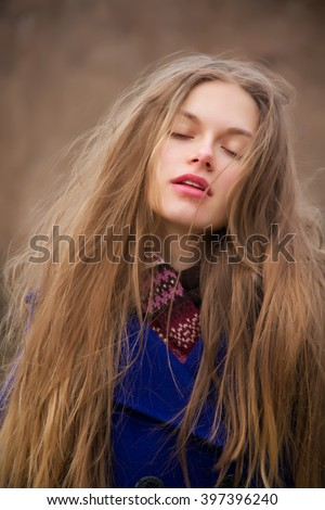 Beautiful young woman with long tangled hair in daydreams. Woman has luxury long blonde hair. She closed her eyes and slightly opened lips. She enjoys and gets pleasure.  - stock photo