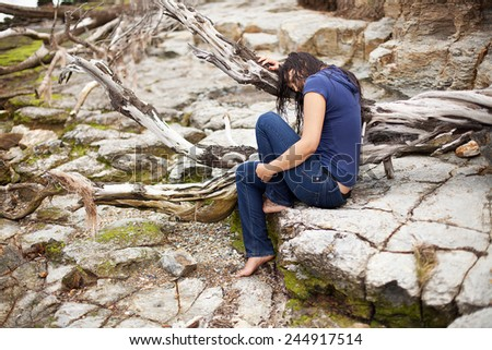 Beautiful young woman with long wet brunette hair sitting on rocks at the edge of the river