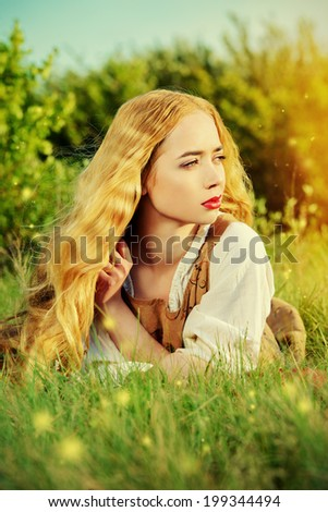 Beautiful young woman with magnificent blonde hair posing outdoor. Countryside, meadow.  - stock photo