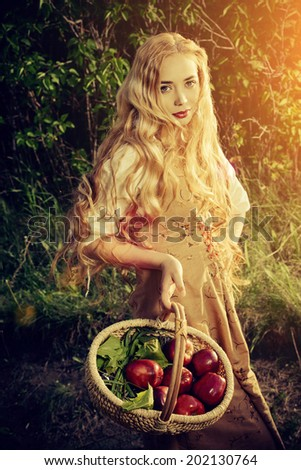 Beautiful young woman with magnificent blonde hair standing outdoor with a basket with apples. Countryside.  - stock photo