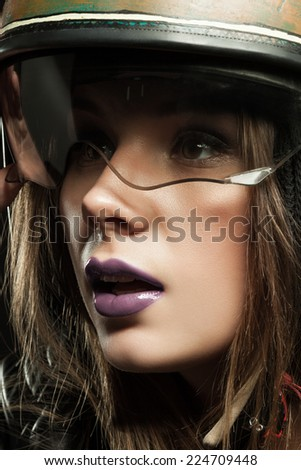 Beautiful young woman with make-up in a motorcycle helmet on a black background closeup - stock photo