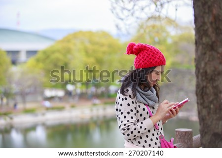 beautiful young woman with maroon beanie hat using smartphone smiling outdoors in park in spring. - stock photo
