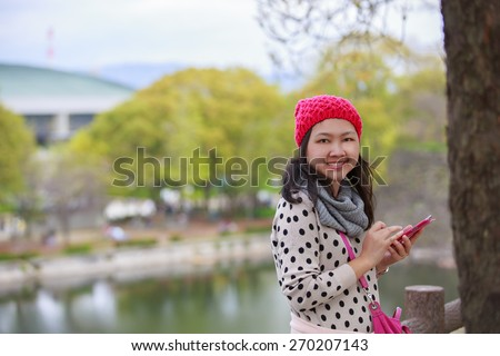 beautiful young woman with maroon beanie hat using smartphone smiling outdoors in park in spring.