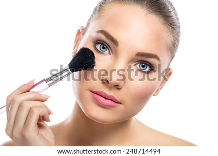 Beautiful young woman with mirror applying powder on cheek - stock photo
