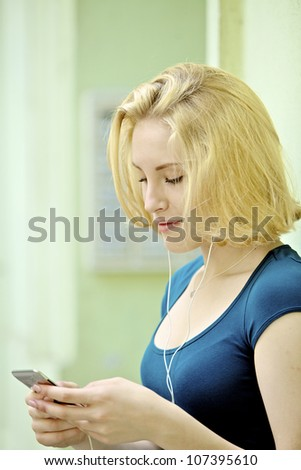 Beautiful young woman with music player - stock photo