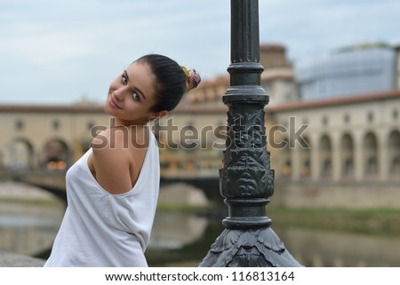 Beautiful young woman with naked shoulder on front side of Arno river, Florence, Italy - stock photo