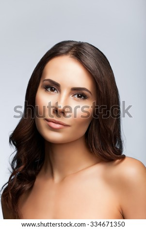 beautiful young woman with naked shoulders, on bright grey background - stock photo