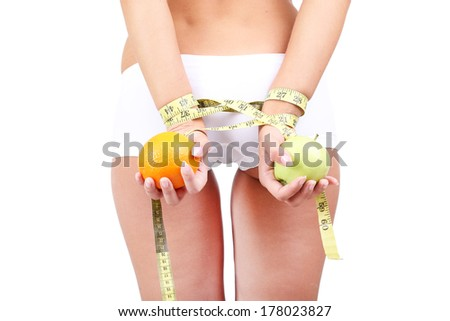 Beautiful young woman with orange and measuring tape on grey background
