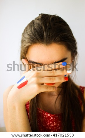 Beautiful young woman with painted french flag on face, hand & manicure, c games supporter - stock photo