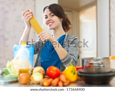 beautiful young woman with pasta and vegetables at her kitchen  at home - stock photo