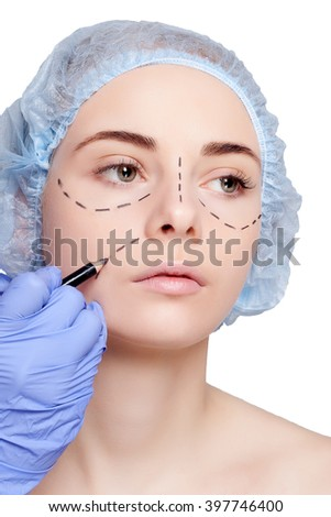 Beautiful young woman with perforation lines on her face before plastic surgery operation. Beautician touching woman face and draws a pencil or marker. studio shot on a white background