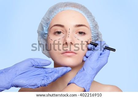 Beautiful young woman with perforation lines on her face before plastic surgery operation. Beautician touching woman face and draws a pencil or marker. - stock photo