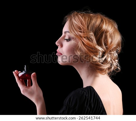 Beautiful young woman with perfume bottle on black background - stock photo