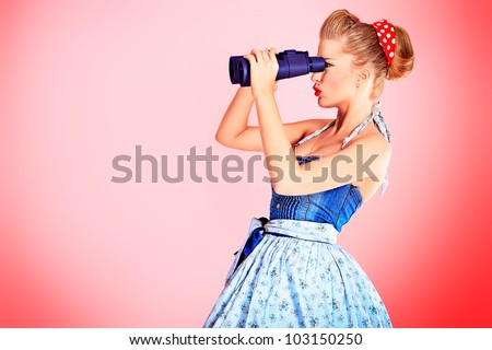 Beautiful young woman with pin-up make-up and hairstyle looking through binoculars. - stock photo