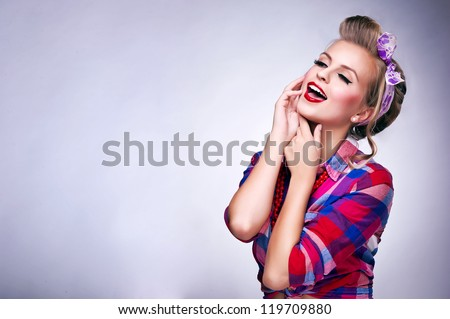 Beautiful young woman with pin-up make-up and hairstyle posing - stock photo