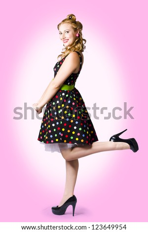 Beautiful Young Woman With Pin-Up Make-Up And Hairstyle Posing In Rockabilly Polka Dot Dress And High Heel Shoes On Pink Studio Background - stock photo