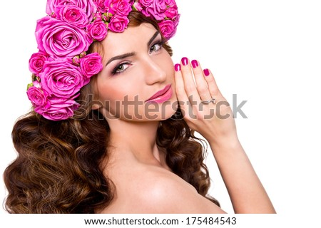 Beautiful young woman with pink manicure, pink lips and pink roses in her hair