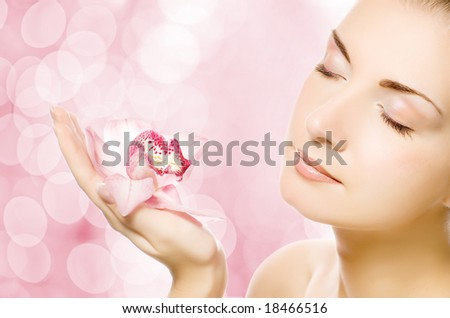 Beautiful young woman with pink orchid over abstract blurred background - stock photo