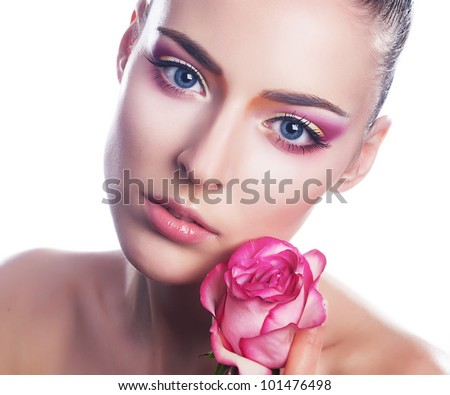 Beautiful young woman with pink rose bud - close up beauty portrait - stock photo