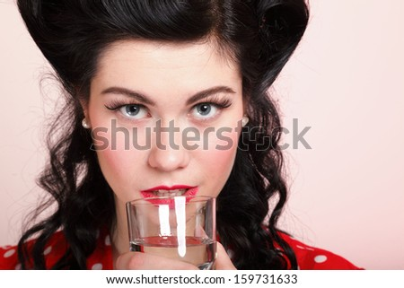 Beautiful young woman with pinup makeup and hairstyle drinking water pink background