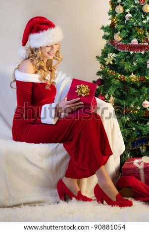 Beautiful young woman with present in christmas eve
