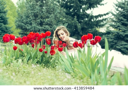 beautiful young woman with pretty smiling face lying in flowerbed with red tulips on green grass in park outdoor - stock photo