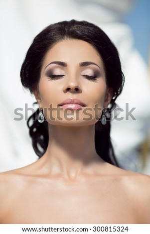 Beautiful Young Woman with professional makeup, eyeshadow, Clean Fresh Skin outdoor close up - stock photo