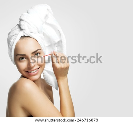 Beautiful young woman with pure healthy skin and removes makeup from the face with a cotton swab on a gray background. - stock photo