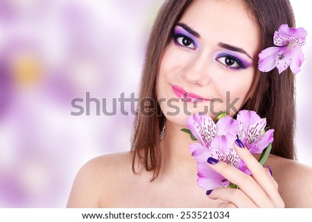 Beautiful young woman with purple flower on bright color background