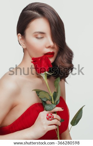 Beautiful young woman with red flowers posing in the studio.