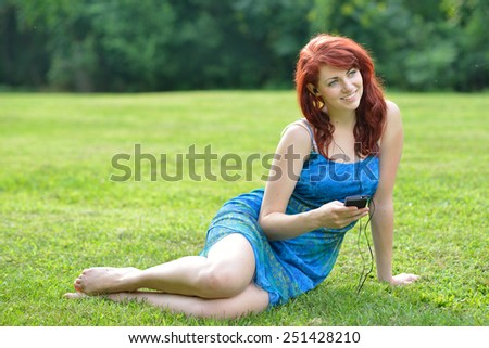 Beautiful young woman with red hair in blue and green sun dress sitting in field listening to music from headphone and portable music player- summer time.  - stock photo