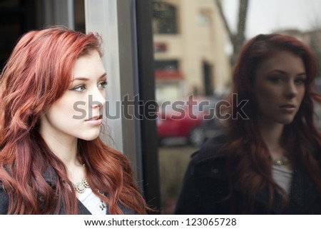Beautiful young woman with red hair reflected in a shop window. - stock photo