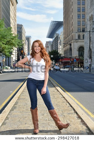 Beautiful young woman with red hair stands in white shirt and blue jeans in city - on median of street - stock photo
