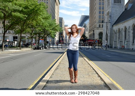 Beautiful young woman with red hair stands in white shirt and blue jeans in city - on median of street