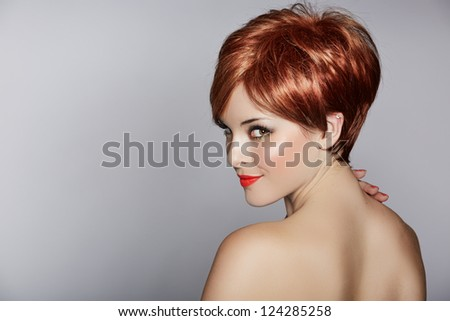 beautiful young woman with red hair wearing short pixie crop hairstyle on studio background - stock photo