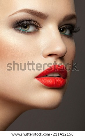 beautiful young woman with red lips, perfect skin. Trendy evening make-up