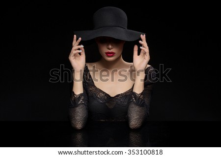 Beautiful young woman with red llips in black hat. Over dark background. Copy space.