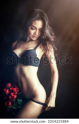 Beautiful young woman with red rose in hand.