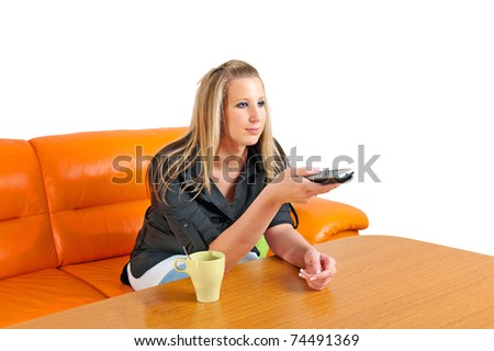 Beautiful young woman with remote control on a sofa in her living room - stock photo