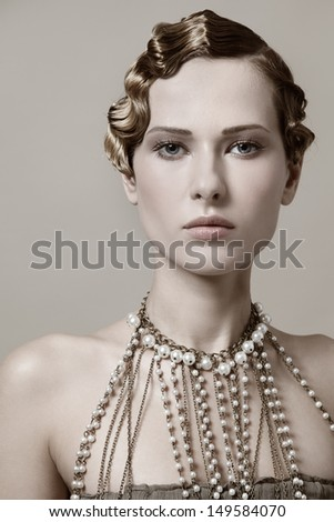 Beautiful young woman with retro hairstyle and fancy necklace - stock photo