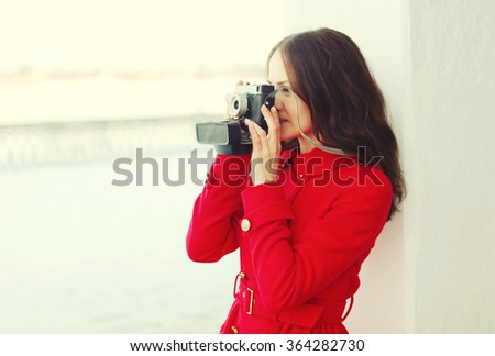 Beautiful young woman with retro vintage camera in winter day, profile view  - stock photo