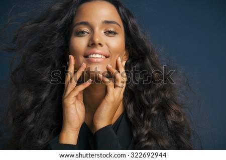beautiful young woman with shine hair and bright makeup touching her face and smiling. Make up and cosmetics concept. studio shot, horizontal - stock photo