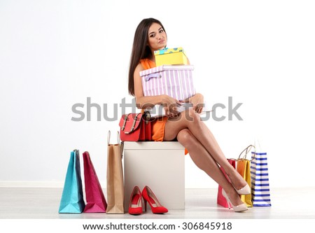Beautiful young woman with shopping bags and boxes isolated on white
